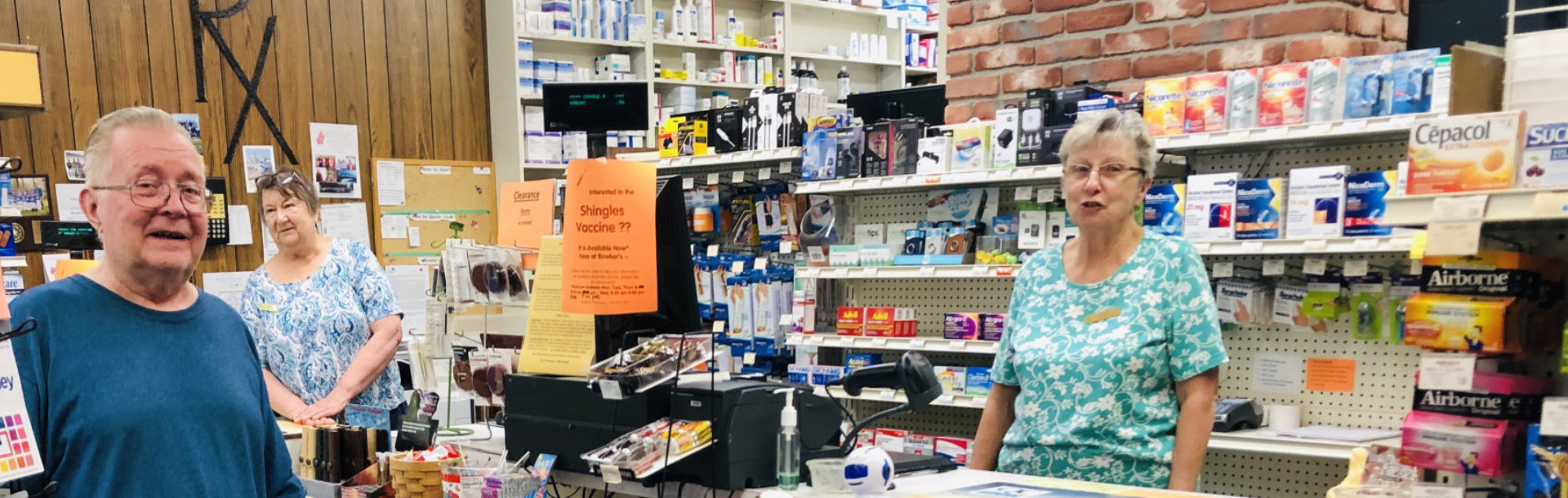 pharmacy personnel and customer posing for the camera